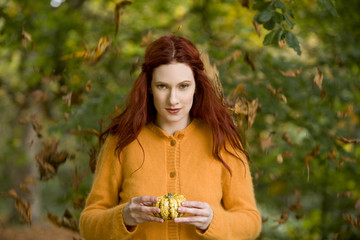 A young woman holding a small pumpkin
