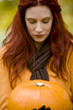A young woman looking at a pumpkin