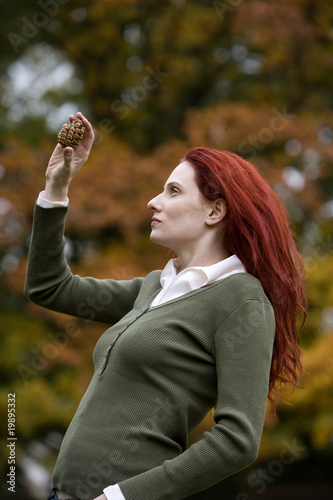 A young woman looking at a pine cone