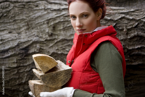 A young woman holding a handful of logs