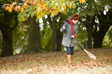 A young woman raking up autumn leaves