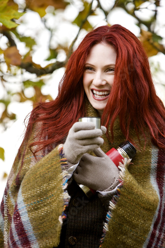 A young woman holding a flask, laughing