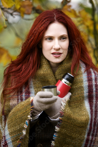 Portrait of a young woman wrapped in a blanket, holding a flask