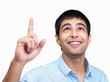Happy young guy pointing upwards against white background