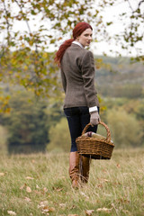 A young woman walking through a field holding a wicker basket