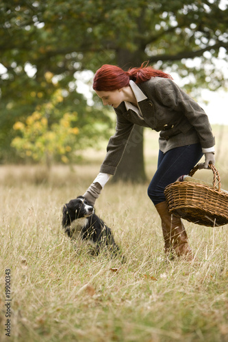 A young woman standing in a field with her dog