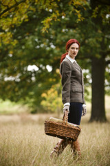 A young woman walking through a field, holding a wicker basket