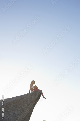 Model sitting on a rock