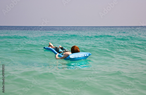 boy is lying at an air-mattress for relaxing at the clear sea