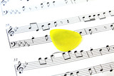 music note paper with yellow guitar pick