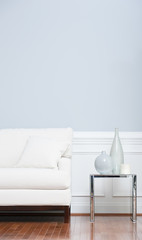 White Sofa and Glass End Table Against Blue Wall