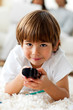 Smiling little boy holding a remote lying on the floor