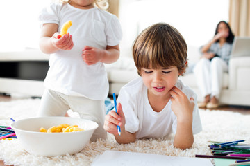 Close-up of siblings eating chips and drawing
