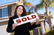 Attractive Hispanic Woman Holding Sold Sign In Front of House