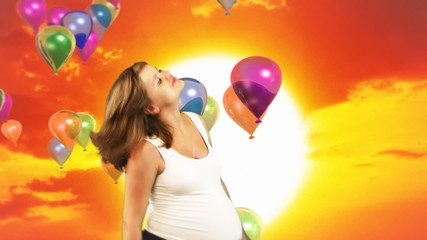 Pregnant woman dancing,sunset and colorful balloons