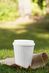 take out white coffee cup in the grass
