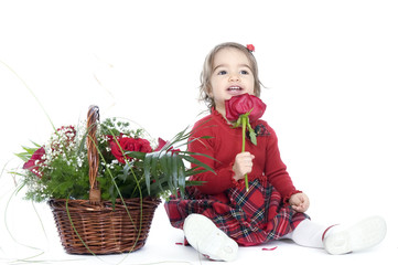 Cute little girl playing with a basket of red roses
