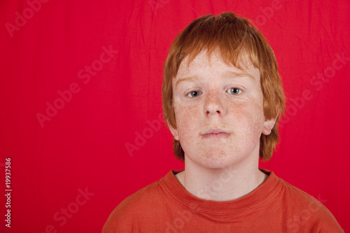 teenage red headed boy with glum facial expression