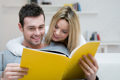 Young couple reading magazine - 19943373