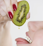 Woman squeezing kiwi into mouth
