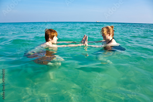 red haired woman and son are enjoying the beautiful clean sea