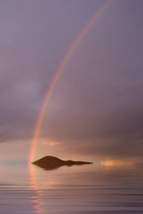Rainbow on the ocean, behind an island.