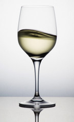 A glass cup of sloshing white wine