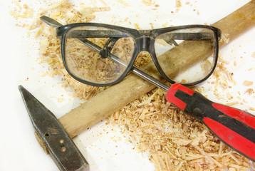Isolated safety glasses, hammer and screwdriver on among sawdust