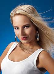 portrait of young pretty blonde on the blue background