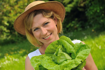 Young woman holding fresh lettuce