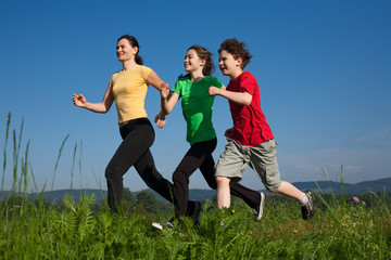 Active family - mother and kids running on green meadow