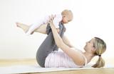 Fototapety junge mama macht mit ihrem baby fitness + yoga uebungen