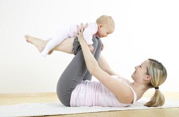 junge mama macht mit ihrem baby fitness + yoga uebungen