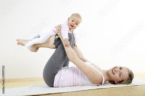 Fototapeta junge mama macht mit ihrem baby fitness + yoga uebungen