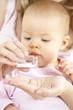 Leinwanddruck Bild - junge mama gibt ihrem baby globuli