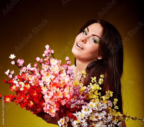 Young woman with group spring flower. Green background.