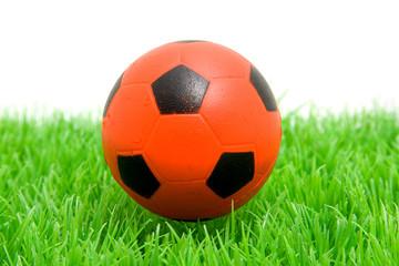 Orange soccer ball on grass over white background