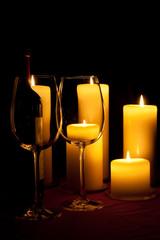 Rotweingläser vor brennenden Kerzen