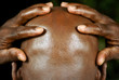 rear view of afro man with hands holding his head