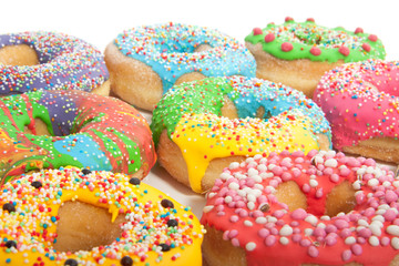 a group of colorful glazed donuts with speckles on top