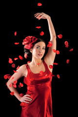 Beautiful flamenco girl with rose petals