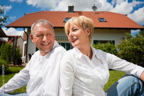 Älteres Paar sitzt vor Eigenheim