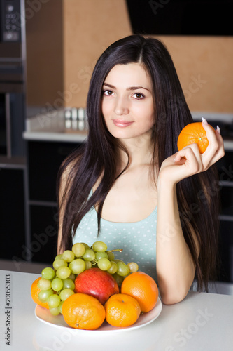Beautiful woman in the kitchen with fruits