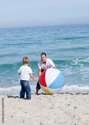 Joyful father and his son playing with a ball