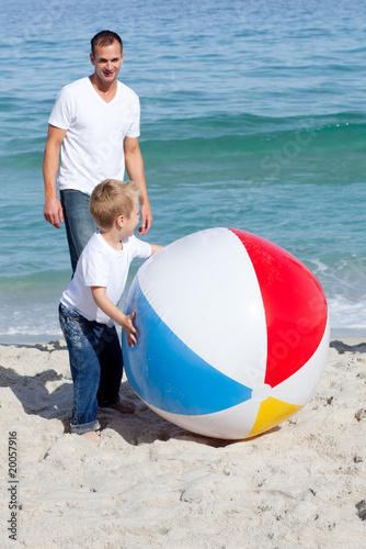 Smiling father and his son playing with a ball