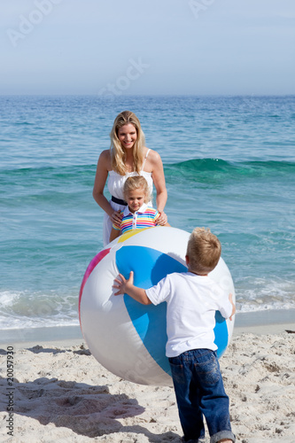 Caring mother and her children playing with a ball