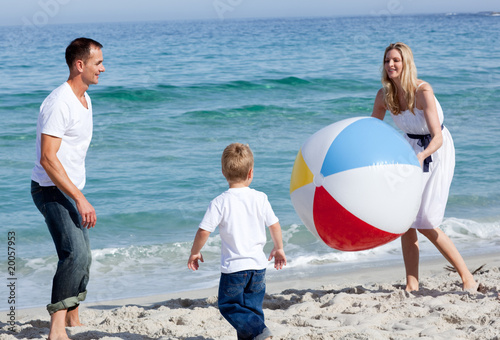 Happy parents and their son playing with a ball
