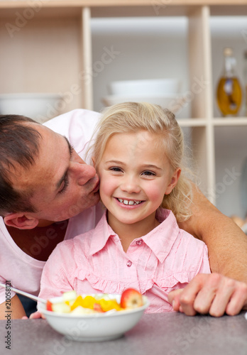 Caring father eating fruit with his daughter