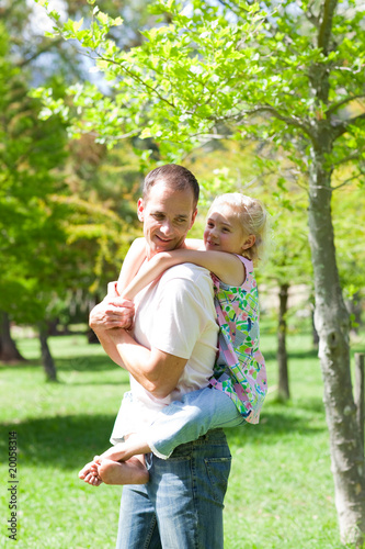 Lively father giving his daughter piggy-back ride