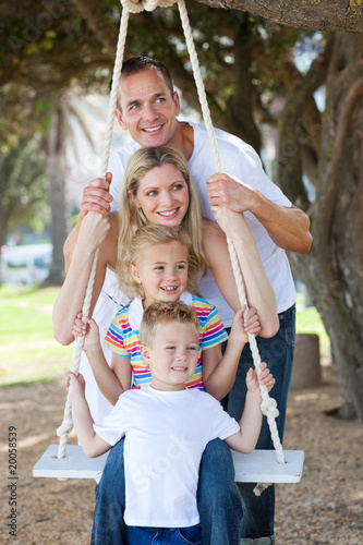 Cheerful family swinging